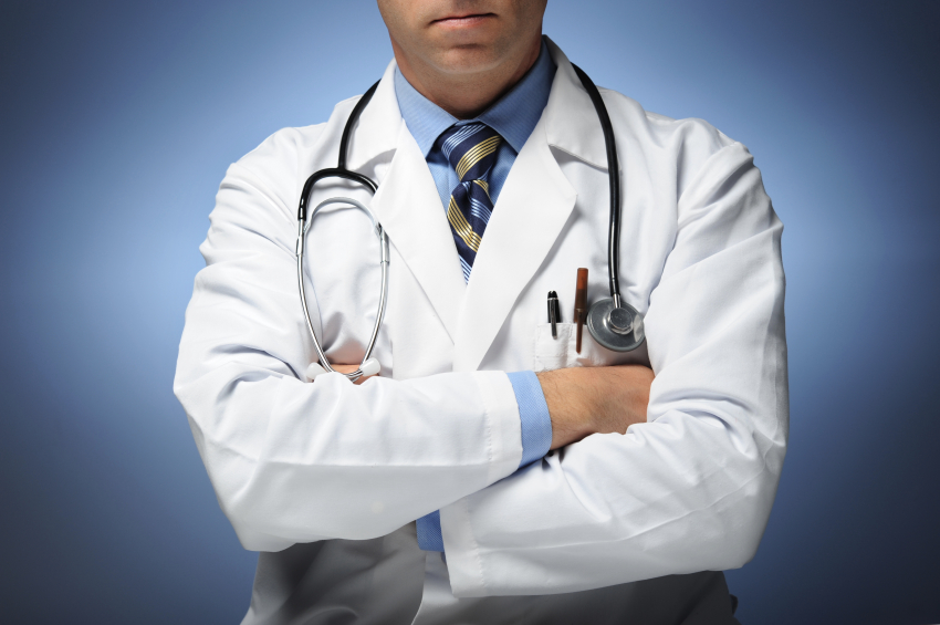 Doctor with arms crossed on blue